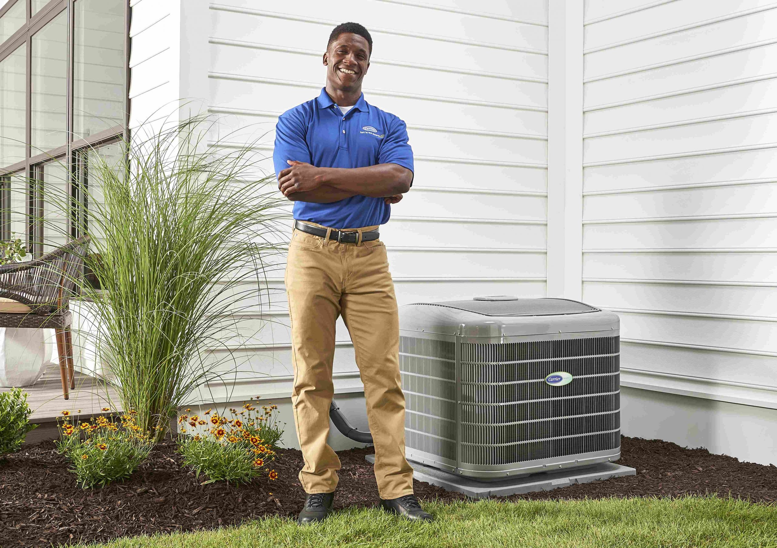 Carrier Technician standing next to air conditioner
